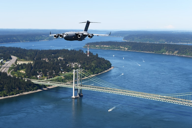 A C-17 Globemaster III from Joint Base Lewis-McChord, Wash., flies over the Tacoma Narrows Bridge in Tacoma, Wash., May 8, 2020. The 62nd Airlift Wing C-17 Demonstartion Team, made up of pilots and loadmasters from the 4th, 7th, and 8th Airlift Squadrons, conducted a flyover of nearly 45 hospitals, healthcare, organizations and landmarks up and down the Puget Sound, in appreciation of those working during the COVID-19 pandemic. (U.S. Air Force photo by Airman 1st Class Mikayla Heineck)