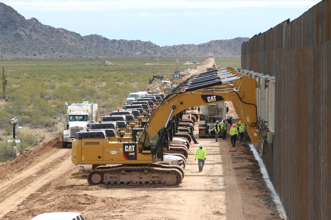 A U.S. Army Corps of Engineers South Pacific Border District contractor's eight excavators hold 32 barrier panels waiting for concrete in the trench to cure near the U.S.-Mexico border at Yuma, Arizona, March 26. USACE is providing direction and oversight for Department of Defense-funded construction of border barrier projects from California to Texas. These projects are being executed by USACE, as directed through the U.S. Army by the Secretary of Defense, in response to the Presidential national emergency declaration dated Feb. 15, 2019, requiring the use of the armed forces and authorizing the use of Section 2808 of Title 10, U.S. Code.