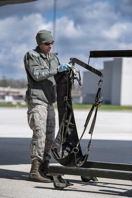 Staff Sgt. Andrew Hall, 445th Aircraft Maintenance Squadron, attaches a C-17 Globemaster III tire onto a hoist here April 9, 2020. 445th Airlift Wing Reservists continue to fly and maintain its fleet of C-17 aircraft, proving they are ready and staying ready despite the COVID-19 crisis. (U.S. Air Force photo/Mr. Patrick O'Reilly)