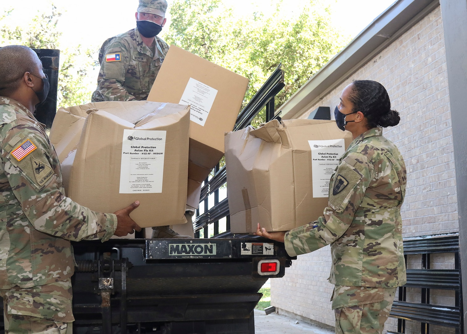 Members of the Texas Military Department's Joint Task Force 176 – Texas State Guard Pfc. Jason Hunter, Texas National Guard Capt. Stephanie Enloe, the task force's medical operations officer, and Sgt. 1st Class Rajendran Kumaraswamy, the task force's medical noncommissioned officer – unload disinfecting kits for Soldiers preparing to support long-term care facility disinfection operations at Camp Mabry in Austin, Texas, May 7, 2020.