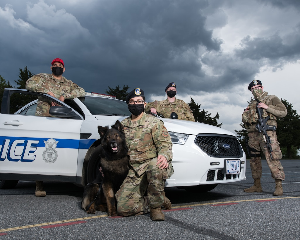 (From left) Staff Sgt. Jose Bracero-Camareno, 436th Security Forces Squadron combat arms instructor; Senior Airman Theresa Braack, 436th SFS military working dog handler with MWD Terry; Staff Sgt. Kirk Savage, 436th SFS Raven team leader and Senior Airman Ryan Claiborn, 436th SFS installation patrolman, stand next to a patrol vehicle May 8, 2020, at Dover Air Force Base, Delaware. The 436th SFS will host events for Police Week 2020 to honor fallen defenders. (U.S. Air Force photo by Mauricio Campino)