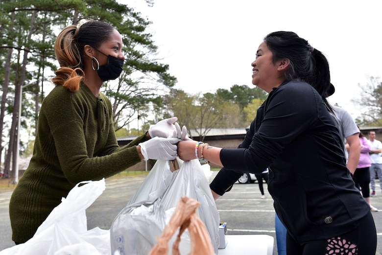 Melanie Simon, left, hands produce to Tina Anderson, during a bi-monthly produce run at Seymour Johnson Air Force Base, N.C. on March 22, 2020.