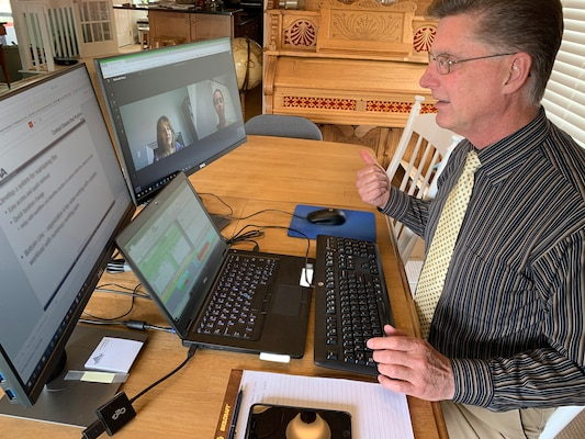 Man sits at his table while teaching training to two female colleagues who appear on his screen monitor