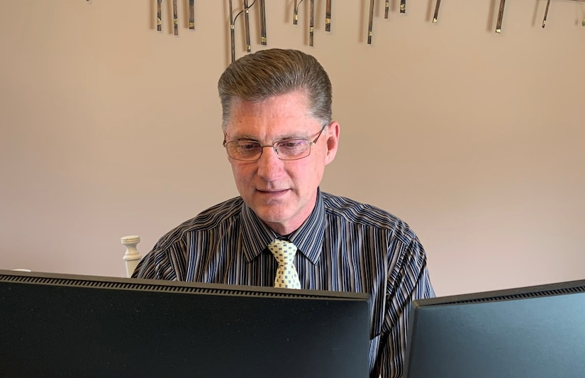 Man sits at his table wearing a dark stripped shirt while working on his computer