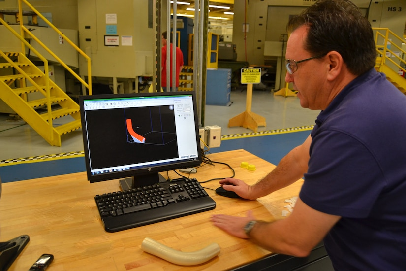 A technician shows a 3D-printed part for a small aircraft.