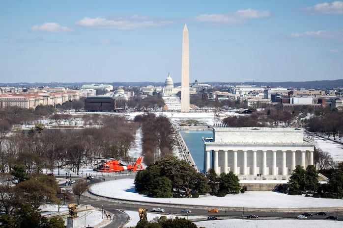 A Coast Guard MH-65 Dolphin helicopter crew from Air Station Atlantic City flies past the Lincoln Memorial and Washington Monument during a patrol in Washington D.C., March 16, 2017.