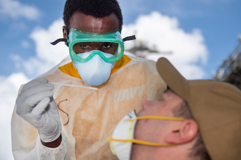 A sailor takes a nasal sample.