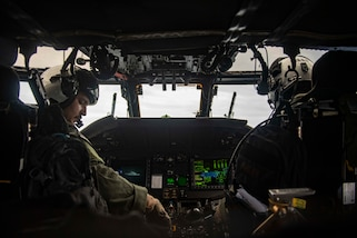 U.S. Navy pilots fly a helicopter.