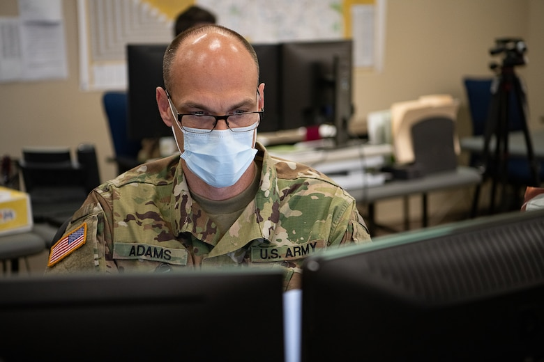 Oklahoma Army National Guard Sergeant 1st Class Michael Adams, senior operations noncommissioned officer assigned to the Oklahoma Joint Task Force, gathers data for current operations reports while working within the Oklahoma Joint Task Force at the Multiagency Coordination Center in Oklahoma City, April 14, 2020. Oklahoma Gov. Kevin Stitt activated 175 additional Oklahoma Army and Air National Guardsmen, April 13, 2020, to aid various missions in support of the state's response to COVID-19. (U.S. Air National Guard photo by Tech. Sgt. Kasey M. Phipps)