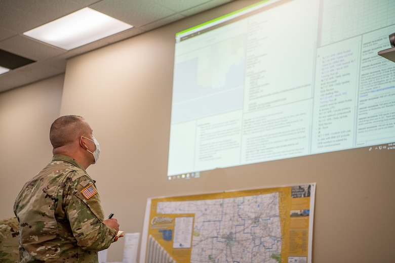 Oklahoma Army National Guard Lt. Jeremie Fisher, a chaplain assigned to the Oklahoma Joint Task Force from the 1st Battalion, 279th Infantry, 45th Infantry Brigade Combat Team, writes down overall Army and Air National Guard numbers and unit assignments from a projection while working within the Oklahoma Joint Task Force at the Multiagency Coordination Center in Oklahoma City, April 14, 2020. Oklahoma Gov. Kevin Stitt activated 175 additional Oklahoma Army and Air National Guardsmen, April 13, 2020, to aid various missions in support of the state's response to COVID-19. (U.S. Air National Guard photo by Tech. Sgt. Kasey M. Phipps)