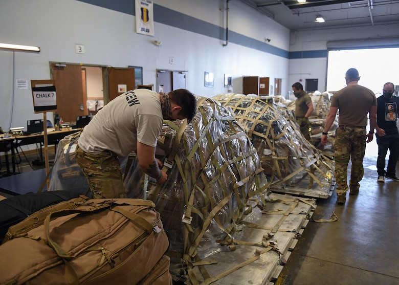Individuals prepare tags and pallets of cargo for deploying personnel.