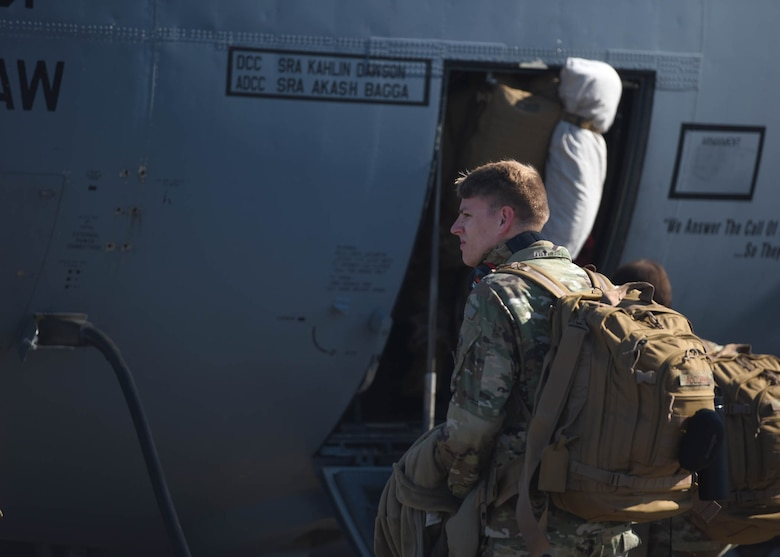 Airmen sit on the ramp of an aircraft before take off
