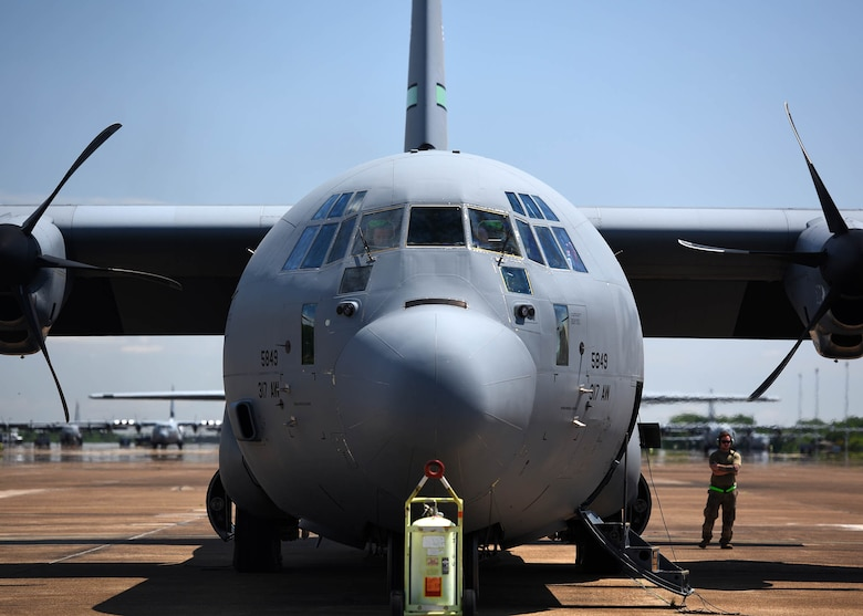 Airmen gather arounf an aircraft before take off