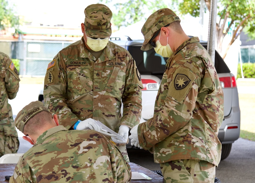 Three National Guard soldiers wear protective equipment.