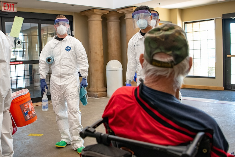 Oklahoma Army National Guardsmen speak with a resident of the Norman Veterans Center in Norman, Oklahoma, April 29, 2020. Guardsmen were at the Center to disinfect commonly touched surfaces and high traffic areas including handrails, chair arms, tables, switches and elevator buttons, split up into three teams, in order to more efficiently covering all of the common areas of the 275,000 square-foot facility. Using pressure sprayers and hand sprayers filled with Centers for Disease Control and Prevention-approved disinfectants, the teams worked from the back of the facility to the front. The residents' military service spans from World War II to Operation Desert Storm. (U.S. Air National Guard photo by Tech. Sgt. Kasey M. Phipps)