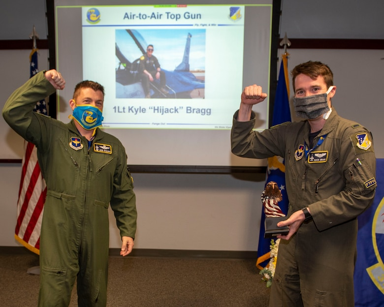 Lt. Col. Jeffrey Shulman, 311th Fighter Squadron commander, presents the Air-to-Air award to 1st Lt. Kyle Bragg, 311th FS Basic Course graduate, during the graduation of B-course Class 19-DBH, May 8, 2020, on Holloman Air Force Base, N.M. Twelve B-course students graduated and will be reassigned to operational flying units throughout the Combat Air Force. (U.S. Air Force photo by Staff Sgt. Christine Groening)