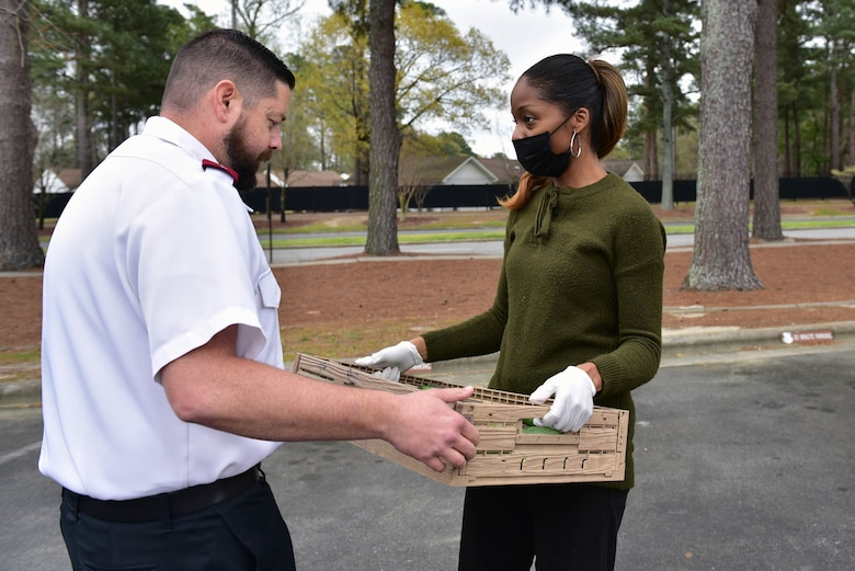 Captain Phillip Stokes, Salvation Army of Goldsboro corps officer, left, accepts donated produce from Melanie Simon at Seymour Johnson Air Force Base, N.C. on March 22, 2020.