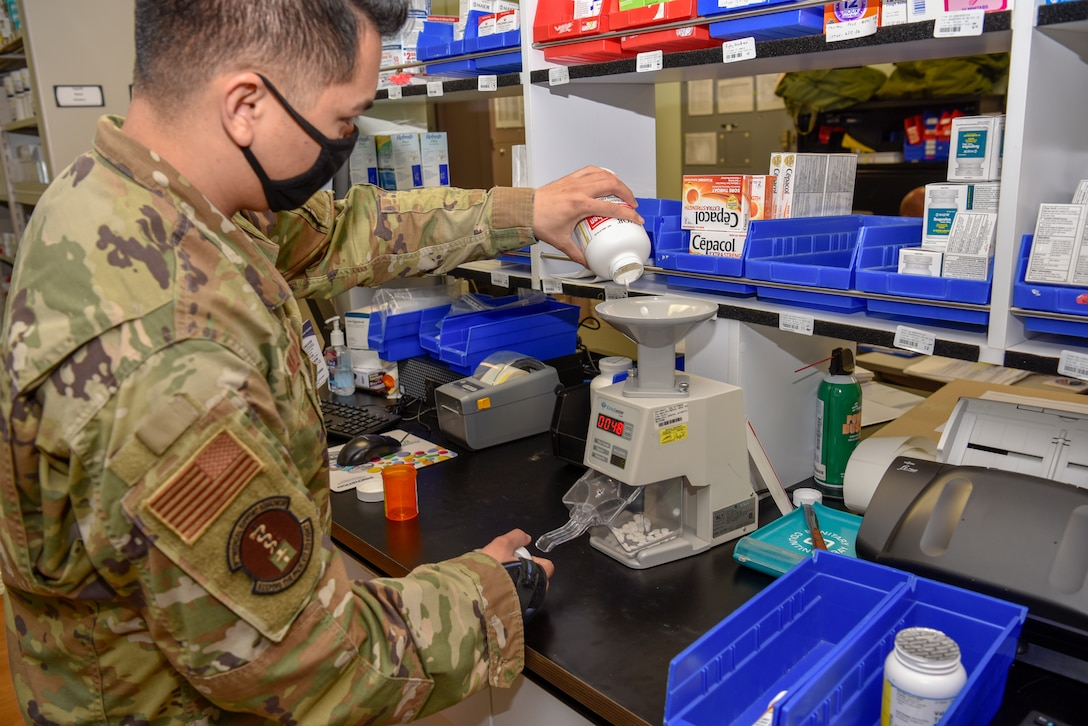 U.S. Air Force Staff Sgt. Albert Vallejo, 8th Medical Support Squadron pharmacy technician, pours medication through a pill counting machine at Kunsan Air Base, Republic of Korea, May 6, 2020. The pharmacy team has a goal time of 20 minutes to fill a prescription to provide a better customer service experience. (U.S. Air Force photo by Tech. Sgt. Joshua Arends)