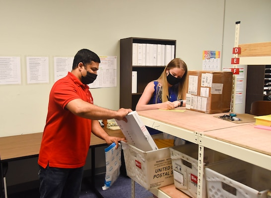 Gaya Gamage (left), and Samantha Schwoerer, U.S. Army Corps of Engineers, Far East District mail clerks, working in mailroom at the district headquarters, Camp Humphreys, South Korea, May 12.