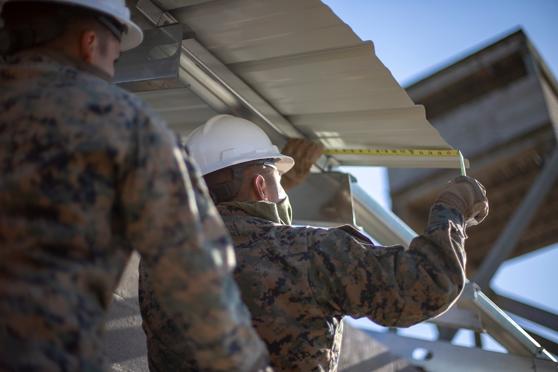 A U.S. Marine measures the overhang of a roof panel during a general exercise at Marine Corps Base Camp Lejeune, North Carolina, April 17.