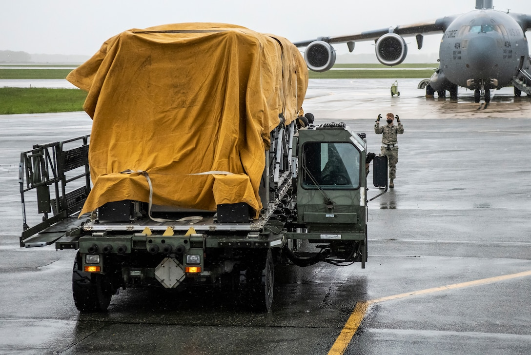A 436th Aerial Port Squadron Airman guides a K-loader at Dover Air Force Base, Delaware, April 30, 2020. Tarps were placed on top of Transport Isolation Systems due to inclement weather at Dover AFB. In accordance with health protection policies, Dover AFB will serve as the sole hub for TIS decontamination on the East Coast. (U.S. Air Force photo by Senior Airman Christopher Quail)