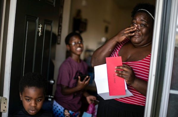 A woman stands in the doorway of her home with her two grade school-aged sons while she holds an envelope holding a letter from her deployed husband.