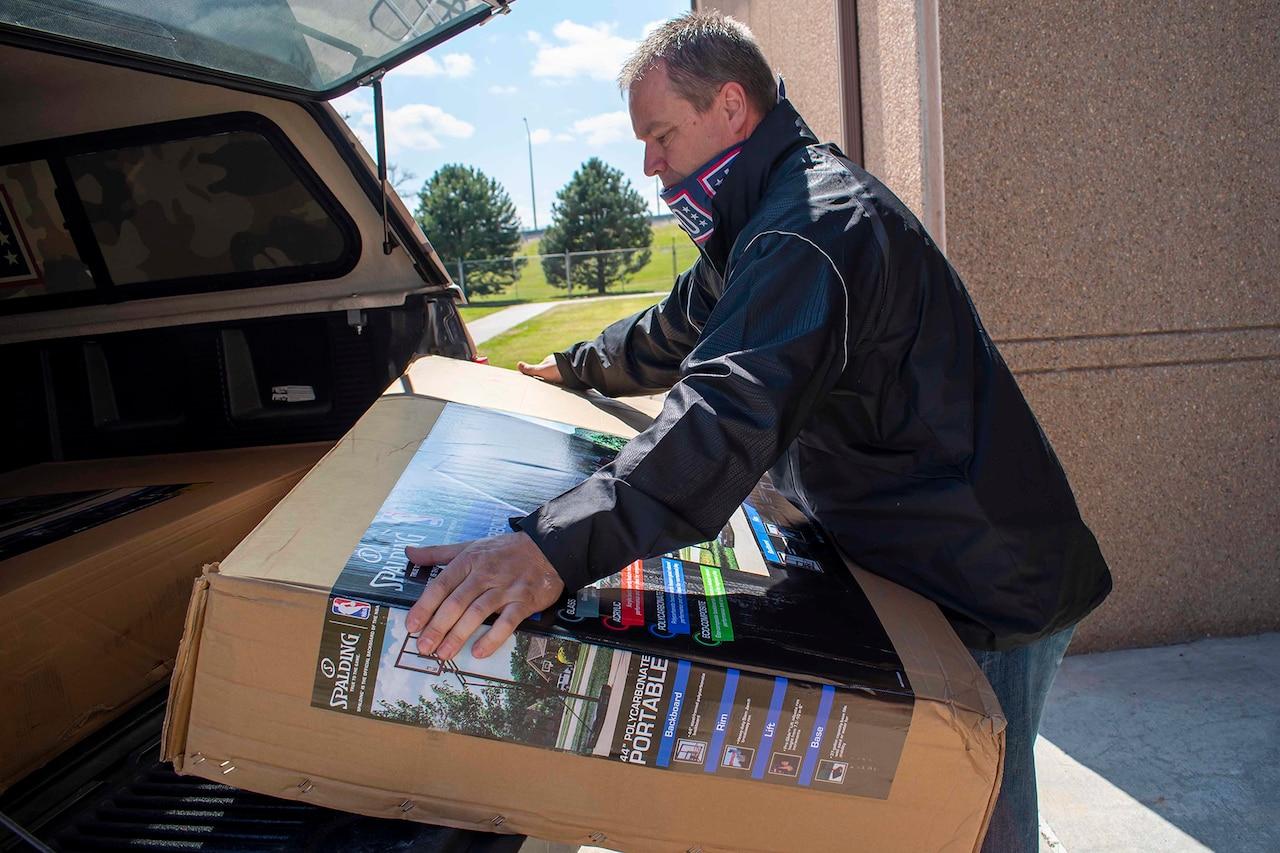 A USO member loading a basketball net into a vehicle.