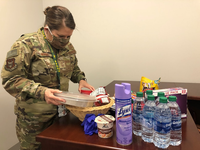 Senior Master Sgt. Tamara Wass, first sergeant for the 419th Aircraft Maintenance Squadron, builds one of several goody baskets for personnel who will self-quarantine on base after returning from deployment
