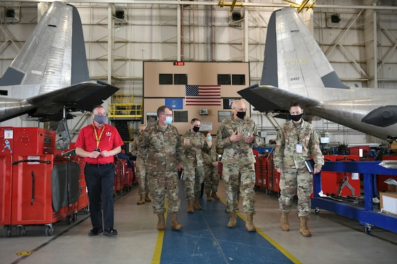 Photo shows Bunch walking with a group of Robins personnel with the tails of two C-130 aircraft in the background.