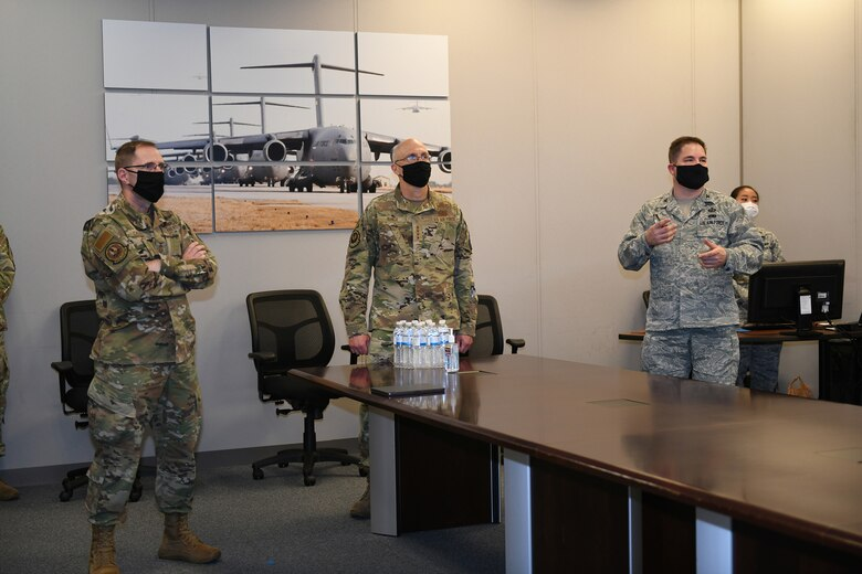 Photo shows the general and chief standing at the head of a conference table with the colonel briefing them.