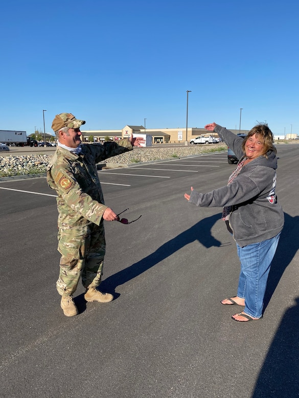 Chief Master Sgt. Craig Fowler, superintendent for the 419th Aircraft Maintenance Squadron, gives his wife, Tammy, a long-distance air hug after arriving home from a six-month deployment to the Middle East.