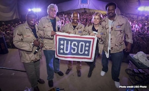 Four men and one woman hold a USO flag with hundreds of troops in the background.