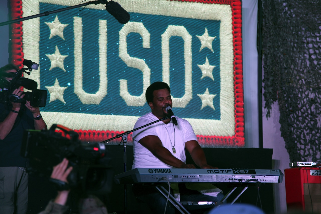 "A man plays a keyboard and sings in front of a giant screen that says ""USO."""
