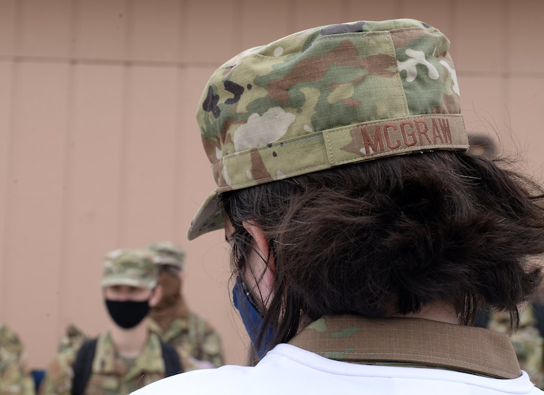 Woman brief other military members wearing mask during COVID-19 pandemic.