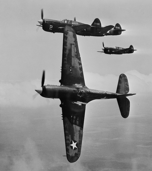 Three P-40F planes flying with one of them flying on its side showing the wings vertical.