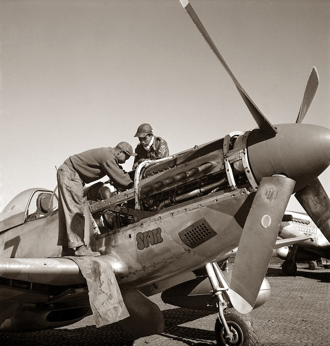 Two soldiers can be seen looking inside a P-51 Mustang