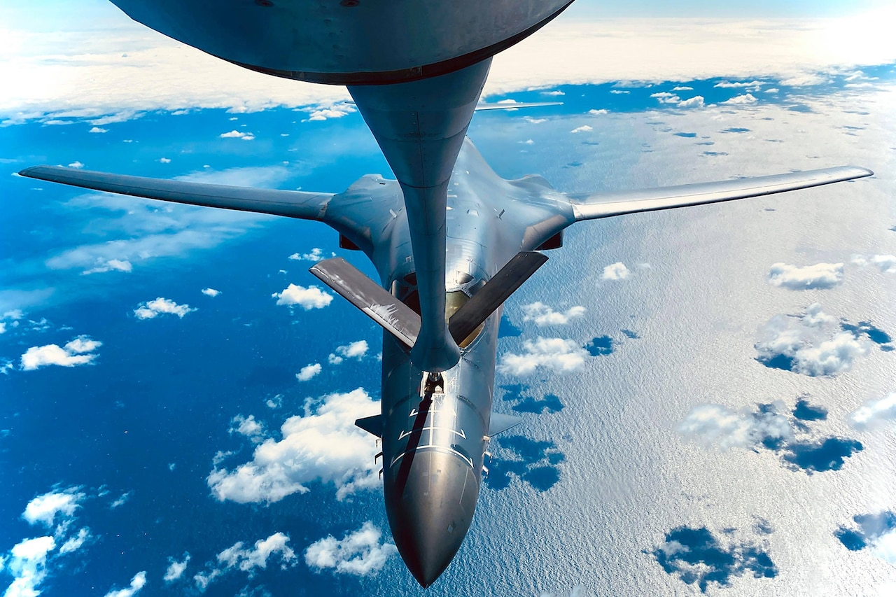 A military aircraft is refueled in midair.