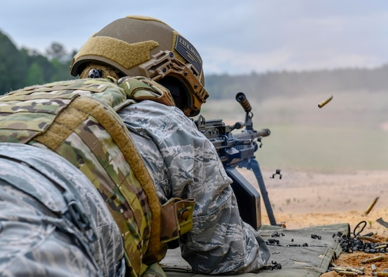 Airman First Class Christopher Eastes, 4th Security Forces Squadron patrolman, fires an M249 light machine gun at Fort Bragg, North Carolina, May 6, 2020. The M249 bolt assembly provides stripping, cambering, firing, and extraction, using the propellant gases and recoil spring for power. (U.S. Air Force photo by Airman First Class Kimberly Barrera)