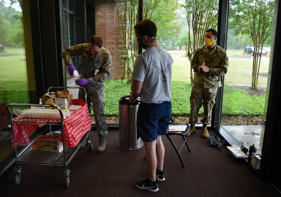 Second Lt. Ian Diebert (left), 14th Operational Medical Readiness Squadron casual, pours coffee for incoming personnel at the entrance of the Koritz Clinic May 8, 2020, on Columbus Air Force Base, Miss. Due to the potential stress enhancers that COVID-19 has caused, the 14th Blaze Medics Morale Council has been consistently looking for ways to uplift the morale within the 14th Medical Group. (U.S. Air Force photo by Airman 1st Class Jake Jacobsen)