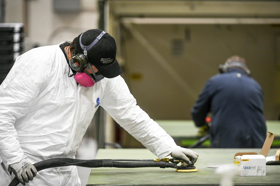 Two workers in the 309th Electronics Maintenance Group sand out walls for a tactical shelter April 29, 2020, at Hill Air Force Base, Utah. The 309th EMXG in the Ogden Air Logistics Complex provides repair and overhaul for exchangeable assets for a multitude of systems on a wide assortment of Air Force weapons systems including fighter aircraft, intercontinental ballistic missiles, powered aerospace ground equipment, tactical shelters, as well as refurbishment of radomes worldwide. (U.S. Air Force photo by Cynthia Griggs)