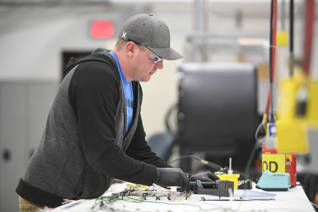 Sean Hamilton, 309th Electronics Maintenance Group, solders a wire harness from the B-809 ground power unit April 29, 2020, at Hill Air Force Base, Utah. The 309th EMXG in the Ogden Air Logistics Complex provides repair and overhaul for exchangeable assets for a multitude of systems on a wide assortment of Air Force weapons systems including fighter aircraft, intercontinental ballistic missiles, powered aerospace ground equipment, tactical shelters, as well as refurbishment of radomes worldwide. (U.S. Air Force photo by Cynthia Griggs)