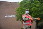 Pfc. Christopher Rodriguez, an Indiana National Guardsman with Alpha Company, 2nd Battalion, 151st Infantry Regiment in Gary, Indiana, directs traffic at a COVID-19 testing site at East Chicago High School, Indiana on May 5, 2020. Governor Eric Holcomb and Indiana University Richard M. Fairbanks School of Public Health aim to examine the prevalence of COVID-19 among Hoosiers through testing at multiple sites around the state. (U.S. Air National Guard photo by Staff Sgt. Justin Andras)