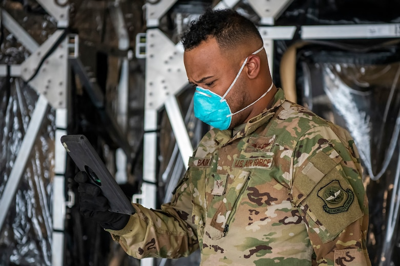 Senior Airman Jashield Blades, 16th Airlift Squadron loadmaster, reviews a checklist at Dover Air Force Base, Delaware, April 30, 2020. Two Transport Isolation Systems were delivered to Dover AFB by a C-17 Globemaster III from Joint Base Charleston, South Carolina. In accordance with health protection policies, Dover AFB will serve as the sole hub for TIS decontamination on the East Coast. (U.S. Air Force photo by Senior Airman Christopher Quail)