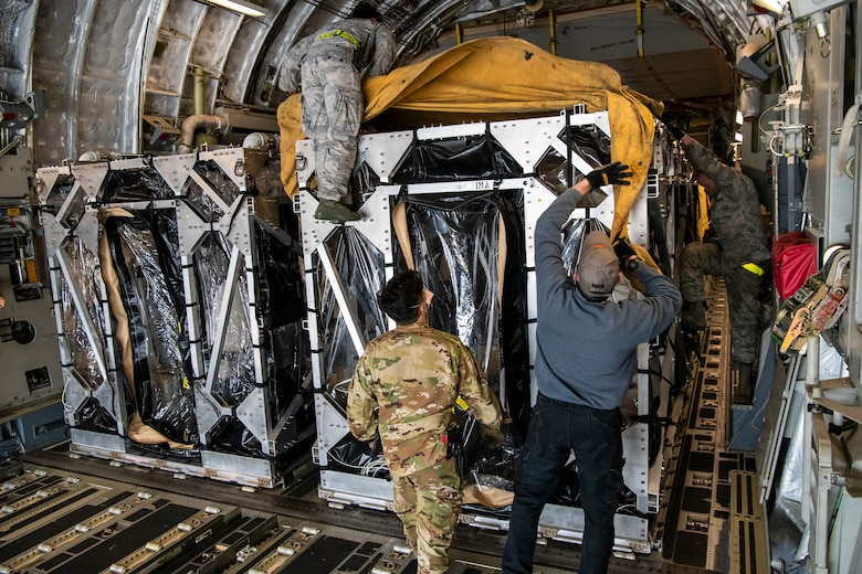 Airmen cover two Transport Isolation Systems with tarps due to inclement weather at Dover Air Force Base, Delaware, April 30, 2020. The TIS units were delivered to Dover AFB by C-17 Globemaster III from Joint Base Charleston, South Carolina. In accordance with health protection policies, Dover AFB will serve as the sole hub for TIS decontamination on the East Coast. (U.S. Air Force photo by Senior Airman Christopher Quail)