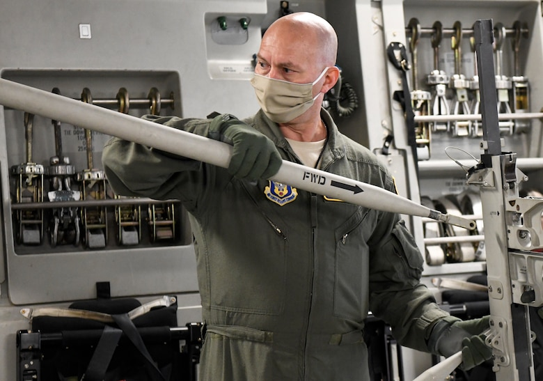 Maj. Mark Dellinger, 36th Aeromedical Evacuation Squadron training flight commander, teaches how to properly build a litter in a C-17 Globemaster III at Dover Air Force Base, Delaware, May 5, 2020. As part of the whole-of-government response to COVID-19, personnel from six different units across the U.S. arrived at Dover AFB and are assigned to two Transport Isolation Systems that will remain at Dover AFB as long as required. (U.S. Air Force photo by Senior Airman Christopher Quail)