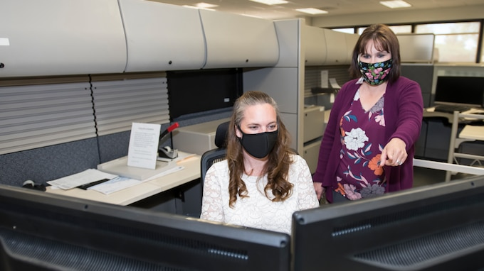Photo shows two women working on a computer while wearing masks.