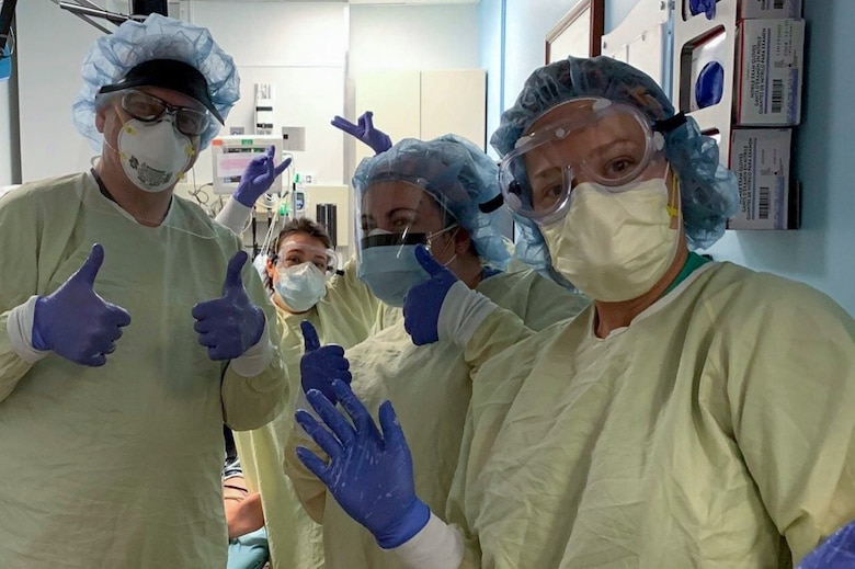 Four medical workers wearing personal protective equipment wave.