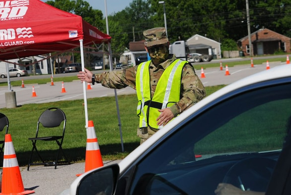 Kentucky National Guard Spc. Robert Acosta directs traffic at Lexington's drive-through testing site. The site is part of Kentucky's efforts to increase COVID-19 testing rates throughout the state.