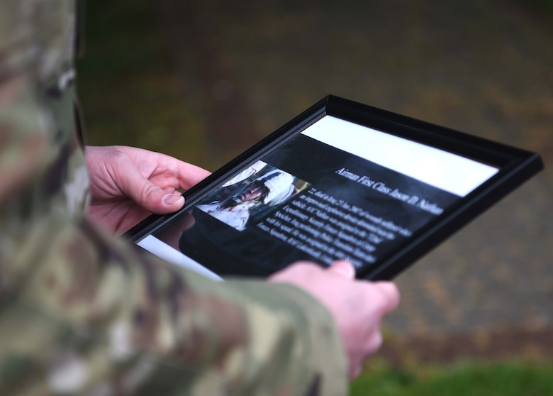 An Airman with the 100th Security Forces Squadron holds a photo of Airman 1st Class Jason D. Nathan during the 100th SFS Memorial Ruck March during National Police Week at RAF Mildenhall, England, May 13, 2020. Nathan, a former 48th Security Forces Squadron Airman, died in Iraq in 2007 from wounds suffered from an IED that detonated near his vehicle. (U.S. Air Force photo by Senior Airman Brandon Esau)