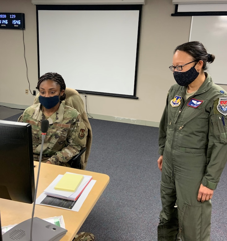 Col. Hui Li, 88th Medical Group's Chief of Aerospace Medicine, 88th Air Base Wing Public Health Emergency Officer and Wright-Patt AFB COVID-19 incident commander, talks with ICC administrative support Senior Airman Quaniesha Swinton, while working in the incident control center. (U.S. Air Force photo/Stacey Geiger)